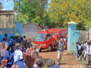 2月にケニアに4台の消防車が到着しました!  塩尻所長、先導をきって登場!!  小学校の子どもたちが歓声でお出迎えです。
